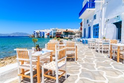 Chairs with tables in typical Greek tavern in Little Venice part of Mykonos town, Mykonos island, Greece