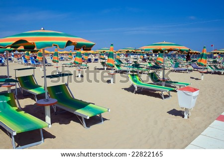 chaise longue and umbrellas on a sandy beach in Rimini, Italy