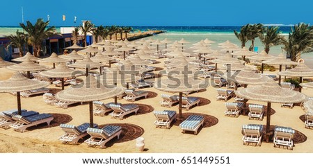 Chaise lounge and parasols on the beach against the blue sky and sea. Egypt, Hurghada #651449551