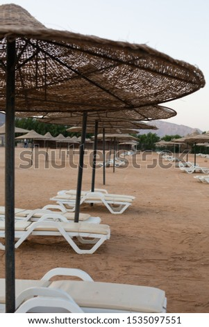 Chaise lounges and straw umbrellas at empty evening beach #1535097551