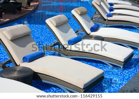 Chaise lounges in swimming pool, Thailand