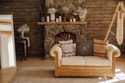 Chalet Cozy Interior Wooden Sofa and Fireplace. Rustic Home Design for Warm Indoor Space Alpine Vacation. Modern Cottage Living Room Decor with Wood Wall and Furniture. Winter Holiday Background