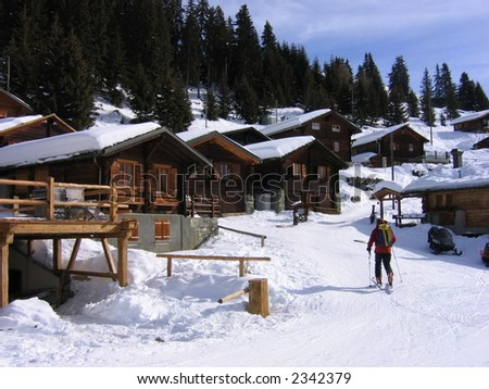 Chalets and a man climbing up the hill on skis, Switzerland