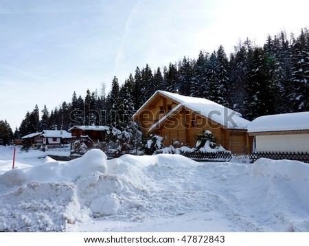 Chalets in Jura mountain Switzerland with lot of snow and fir trees forest behind - stock photo