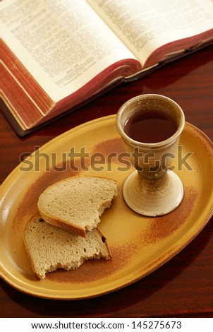 Chalice, bread and open Bible on a table.