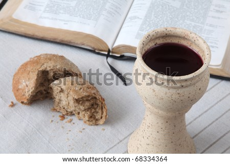 Chalice with red wine, bread and Holy Bible on a tablecloth. Shallow dof