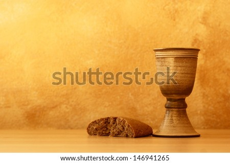 Chalice with wine and bread. Background with copy space.