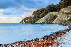 Chalk cliffs in Jasmund National Park. Coastline on the island of Ruegen. Morning mood with calm sea and dramatic clouds. Deciduous trees on the cliff in autumn mood