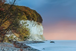 Chalk cliffs on the island of Ruegen. Coastline in autumn in the morning. Trees and stony coastline with leaves and smooth water surface