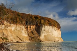 Chalk cliffs on the island of Ruegen. Sunshine and blue sky with clouds on the Baltic Sea coast. Trees and beach section in autumn from the Jasmund National Park