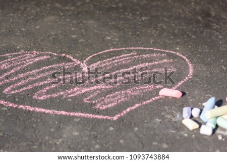 Chalk drawn pink heart on dark grey asphalt #1093743884