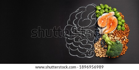 Chalk hand drawn brain picture with assorted food for brain health and good memory: fresh salmon, vegetables, nuts, berries on black background. Foods to boost brain power, top view, copy space