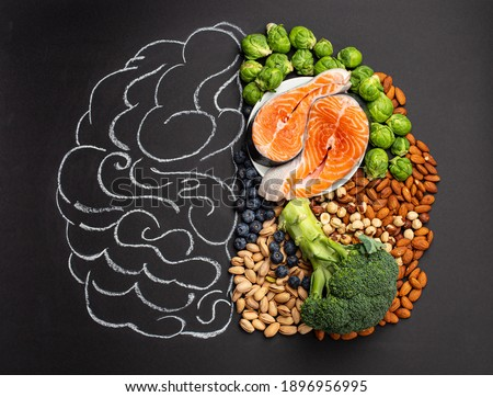 Chalk hand drawn brain with assorted food, food for brain health and good memory: fresh salmon fish, green vegetables, nuts, berries on black background. Foods to boost brain power, top view
