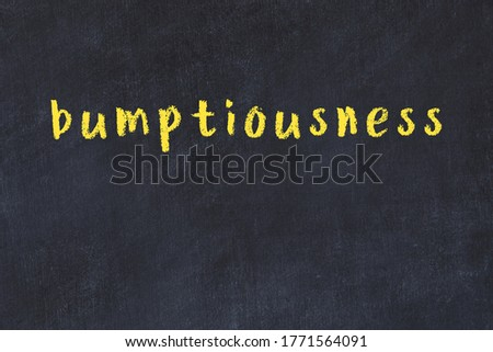 Chalk handwritten inscription bumptiousness on black desk Stock photo ©