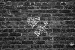 Chalk hearts on a brick wall in black and white.