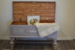 Chalk painted cedar chest, stenciled, open decorated with a framed picture and warm woven blanket.