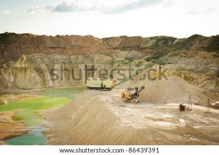 Chalk quarry landscape with big excavator