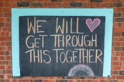 Chalk sign saying will get through this together on a brick wall.  Written during the Coronavirus pandemic lockdown.