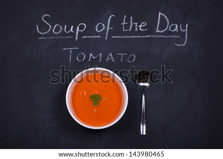Chalkboard advertising the tomato as soup of the day, with a bowl of tomato soup and spoon, garnished with parsley.