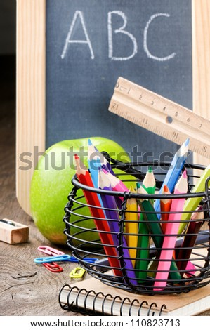 Chalkboard and colorful crayons on wooden desk