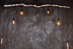 Chalkboard black background texture compose wtih open light bulb and wooden stick. Copy space