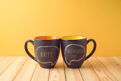 Chalkboard coffee mugs on wooden table with happy friendship day text. Friendship day concept