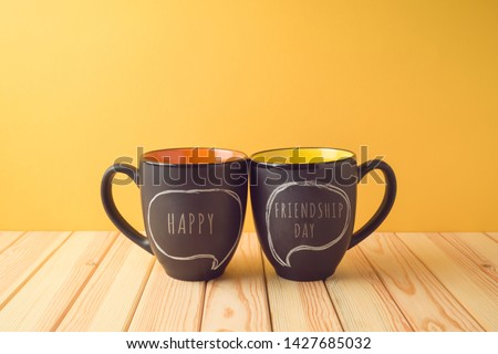 Chalkboard coffee mugs on wooden table with happy friendship day text. Friendship day concept #1427685032
