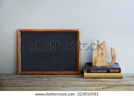 chalkboard frame on the grey wall with books and cat. scandinavian style interior