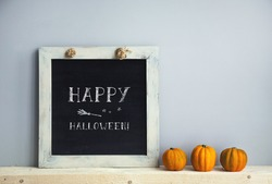 chalkboard frame on the grey wall with books  pumpkins. HAPPY HALLOWEEN