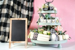 Chalkboard sign with on-trend farmhouse aesthetic three tiered tray decor filled with white pumpkins, cute black plaid gnomes, and farmhouse style stack of books mockup. Modern blush pink background.