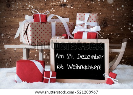 Chalkboard With German Text Am 24. Dezember Ist Weihnachten Means December 24th Is Christmas Eve. Sled With Christmas And Winter Decoration And Snowflakes. Presents On Snow.
