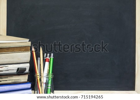 Chalkboard with pecil, pen, books on wooden table. Education concept.  #715194265