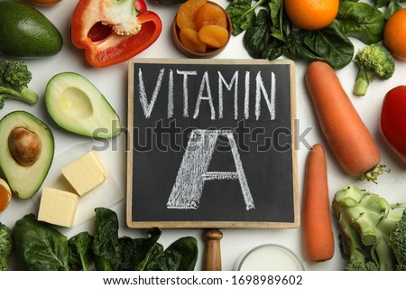Chalkboard with phrase VITAMIN A and fresh products on white table, flat lay