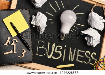 Chalkboard with wrinkled paper, notepad, pen, numerals and lamp. Process of business idea creation. Creasy paper by light bulb with stationery on grey blackboard background. Business idea concept
