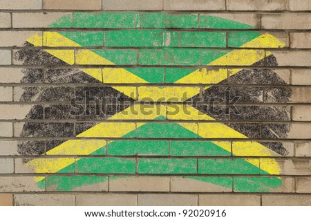 Chalky jamaican flag painted with color chalk on grunge old brick wall