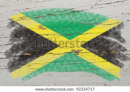 Chalky jamaican flag painted with color chalk on grunge wooden texture