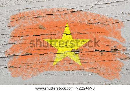 Chalky vietnamese flag painted with color chalk on grunge wooden texture