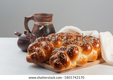 Challah bread with poppy and sesame seeds. Covered with white cover. On white and grey background.