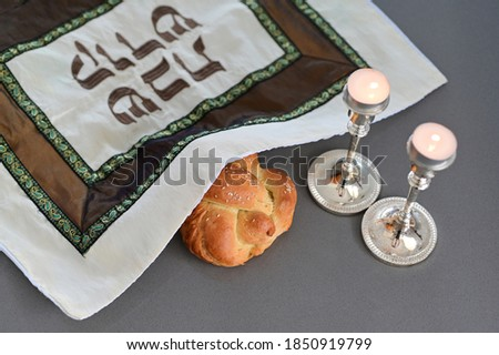 Challah (Jewish bread) with cover  with Hebrew text reading 'Holy Sabbath' beside two lit candles on Sabbath eve Jewish Holiday (Judaism's day of rest on the seventh day of the week - Saturday) Photo stock ©