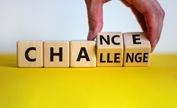 Challenge or chance symbol. Businessman turns cubes and changes the word 'challenge' to 'chance'. Beautiful yellow table, white background, copy space. Business and challenge or chance concept.