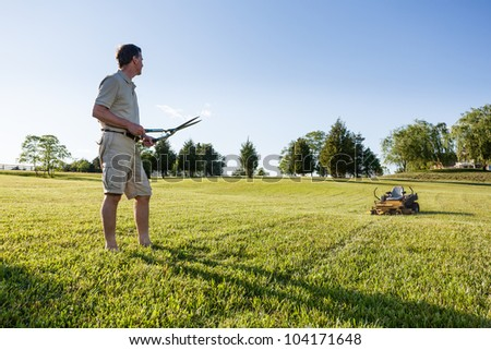 Challenging task of cutting large lawn with grass shears by hand with mower in background #104171648