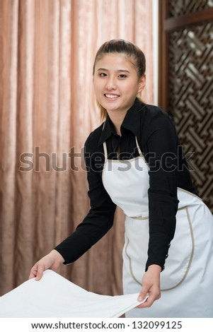 Chamber maid working and looking at camera