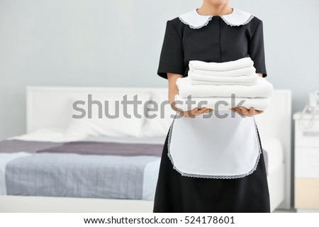 chambermaid holding pile of...