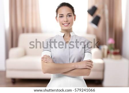 Chambermaid standing on living room background Сток-фото ©