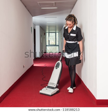 Chambermaid woman cleaning in a hotel with vacuum cleaner.