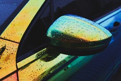 Chameleon holographic colour car after the rain. Side mirror with water drops closeup. Car wrapping. Rainy day.