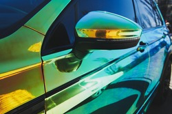 Chameleon holographic colour car. Side view. Driver's door and side mirror. closeup. Car wrapping. Car exhibition.