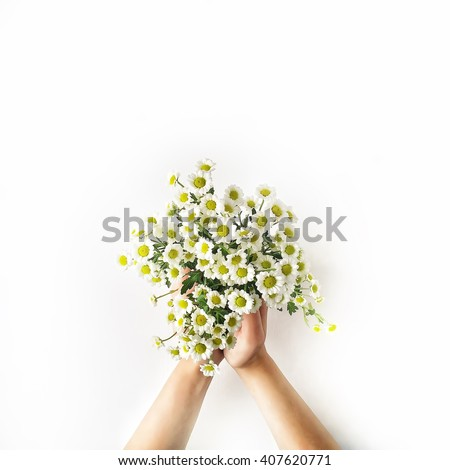 Chamomile bouquet in girl\'s hands on white background. Flat lay, top view