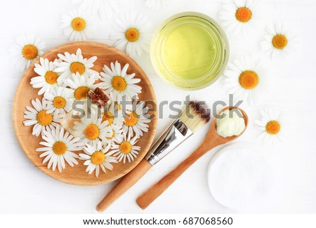 Chamomile flowers and extracted cosmetic beauty products top view. Essential oil, tonic, facial mask, brush and spoon. Botanical skincare preparation. Herbal spa treatment  #687068560