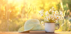 chamomile flowers in Cup, old book, braided hat in garden. Beautiful Rustic Summer landscape with daisy. copy space